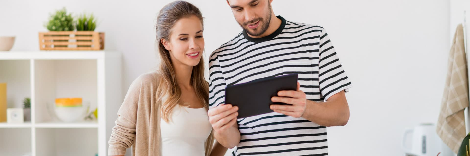 couple in kitchen looking at ipad