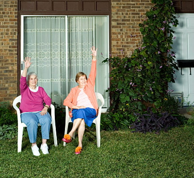 two older ladies waving from their front yard